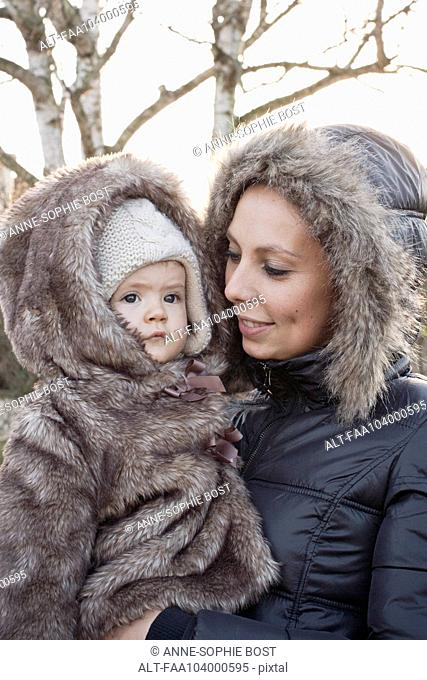Mother and baby girl dressed in winter coats, portrait
