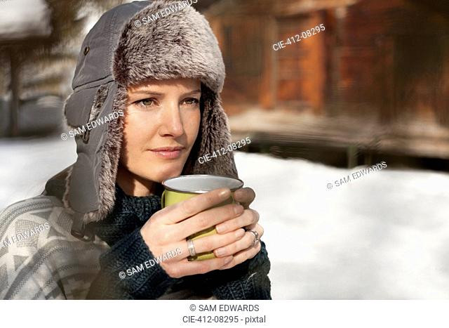 Pensive woman in fur hat drinking coffee outside cabin