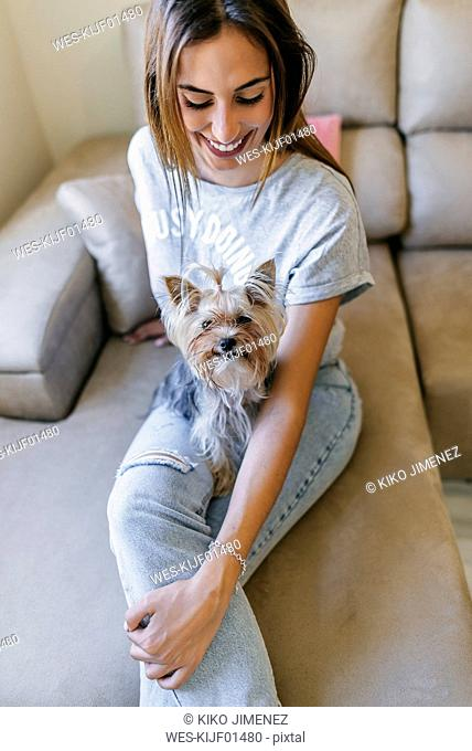 Smiling young woman sitting on couch with her Yorkshire Terrier