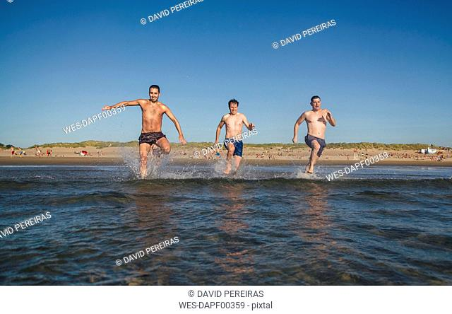 Friends running and jumping into the sea