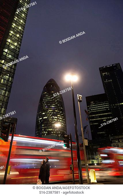 London, UK, The City - Two red Double-decker buses zipping in front of pedestrians close to the Gherkin Building at night