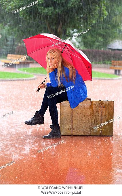 Austria, Thalgau, teenage girl with red umbrella sitting on her suitcase in the rain