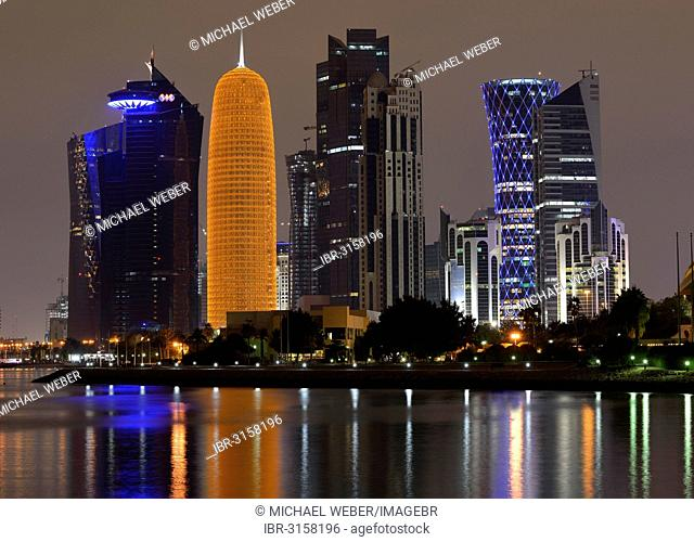 Night scene, skyline of Doha with Al Bidda Tower, World Trade Center, Palm Tower 1 and 2, Burj Qatar Tower with golden illumination and Tornado Tower