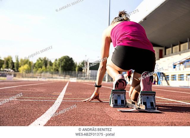 Female runner on tartan track in starting position