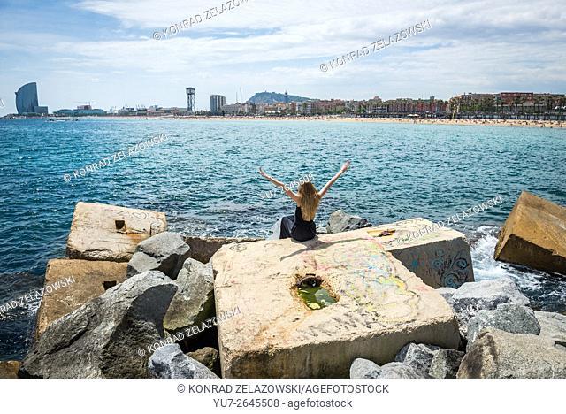 Woman sitting on breakwater on the beach in La Barceloneta neighborhood, Barcelona, Spain