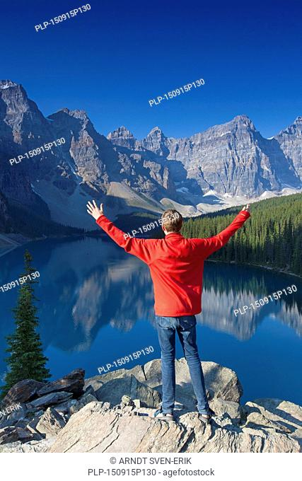Tourist with open arms on look-out point looking over Moraine Lake in the Valley of the Ten Peaks, Banff National Park, Alberta, Canada