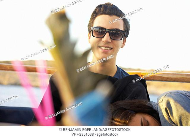 appy smiling young student man relaxing with girlfriend and sunglasses in bar in Malta