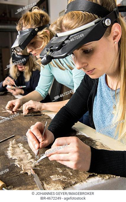 Restoration studio, women, restorers restore lent scarf on worktable in Atelier, Munich, Bavaria, Germany