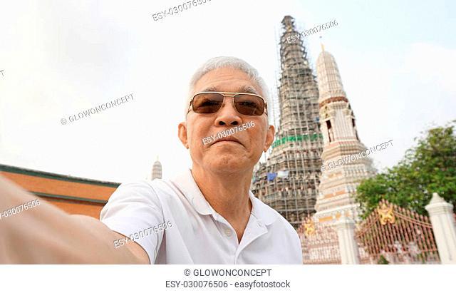 Asian senior man selfie at temple of dawn landmark of Bangkok Thailand