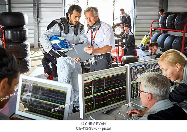 Manager and formula one driver discussing telemetry diagnostics in repair garage