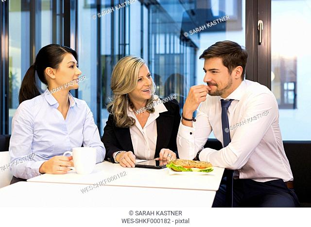 Businesspeople having lunch break with digital tablet in canteen