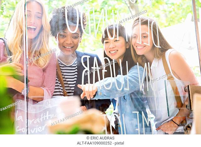 Young women looking through shop window together