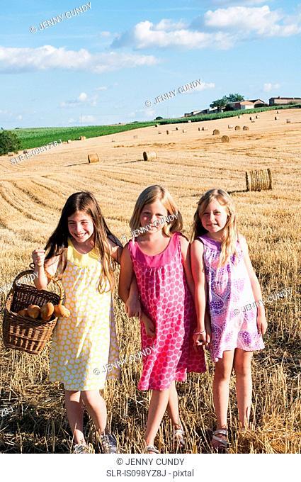 Three girls standing in field, portrait