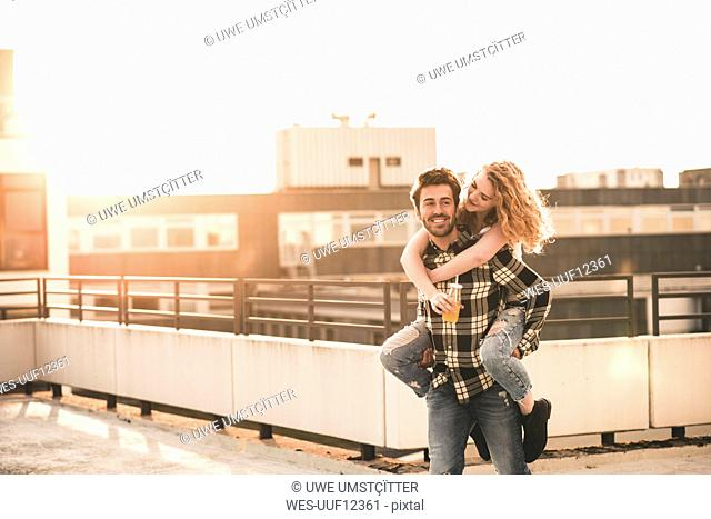 Portrait of young man giving his girlfriend a piggyback ride on roof terrace at sunset