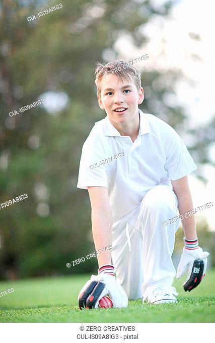 Boy kneeling on cricket pitch