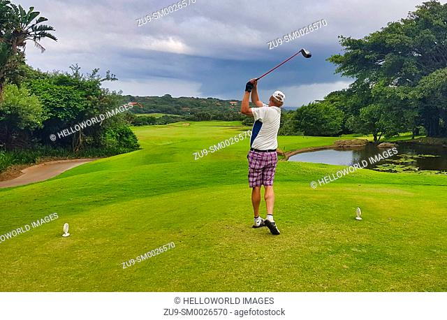 Rear view of golfer teeing off at Zimbali Golf Course, Ballito, KwaZulu Natal, South Africa