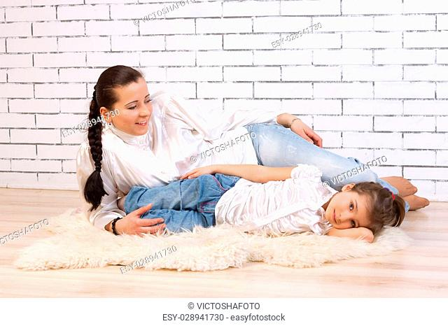 Mother and 5 year old daughter lying on a white fur rug beside the white stone wall