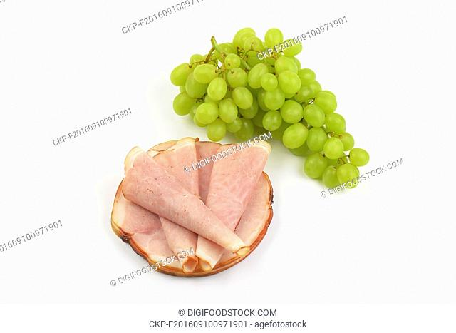 stack of ham slices and bunch of white grapes on white background