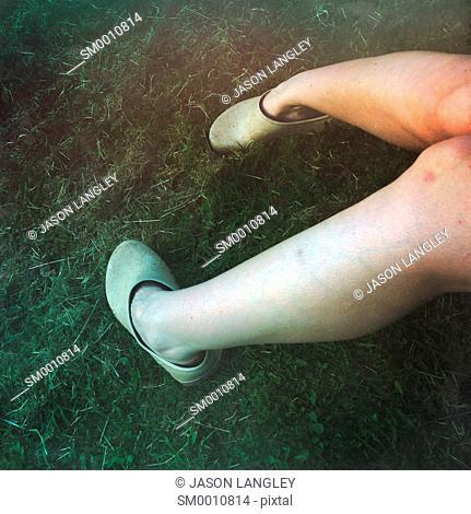 Woman's legs in grass wearing gardening clogs