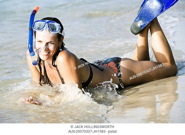 Mid adult woman wearing snorkeling gear and lying on the beach