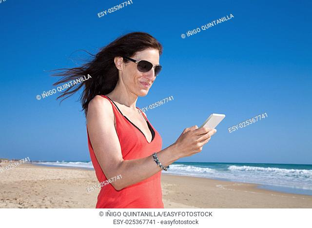portrait of brunette woman with black sunglasses and red shirt smiling and touching mobile phone smartphone at beach