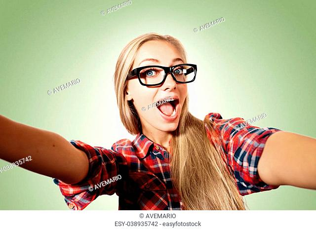 Close up portrait of a young joyful blonde girl holding a smartphone digital camera with her hands and taking a selfie self portrait of herself standing against...