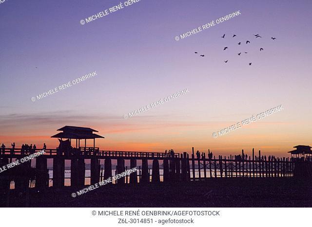 Sunset over the lake near wooden foot bridge U Bein Bridge crossing the Taungthaman Lake near Amarapura in Mandalay Myanmar