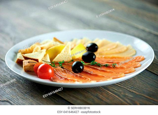 Close-up of white plate with the delicios appetizers set: fresh tomatoes,black olives, white bread pieces, smoked salmon slices and cheese