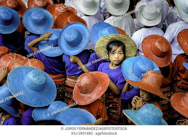 A girl looking to the camera among the many children with colourful hats in a celebration