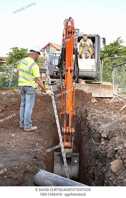 workman measures the depth of a trench dug by a jcb