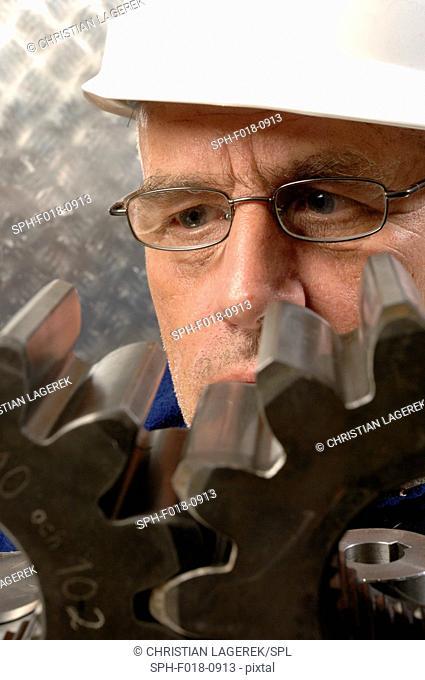MODEL RELEASED. Engineer scrutinising metal cogs