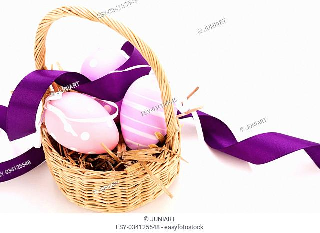 Close-up of a straw basket with traditional Easter eggs painted in pastels and decorated with a mauve ribbon, on white background
