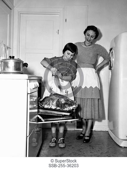 Mother looking at her daughter basting a turkey