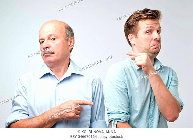 Portrait of two caucasian men pointing finger on each other. It was not me, he did it concept