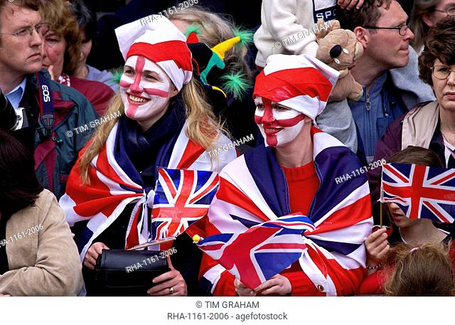 Enthusiastic patriots wearing Union Jack flags and England flag symbols painted on their faces, London, England
