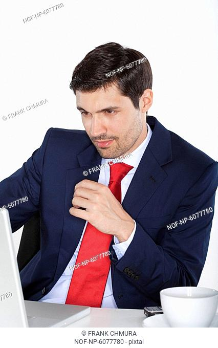 young business executive in suit behind desk with laptop