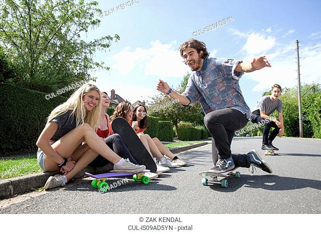 Four young women sitting on kerb watching skateboarders