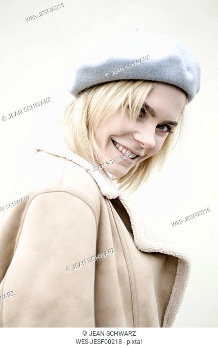 Portrait of smiling blond woman wearing coat and beret