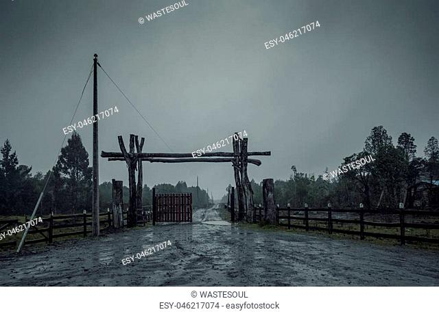 Wet country road leading to the half-opened wooden gates in desperate gray shades