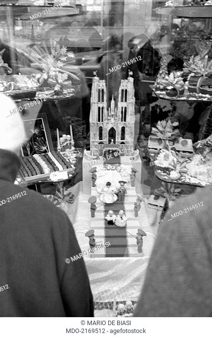 Cake shop showing a wedding cake depicting the cathedral of Saint Michael and Saint Gudula in the shop window. Brussels, 1960s