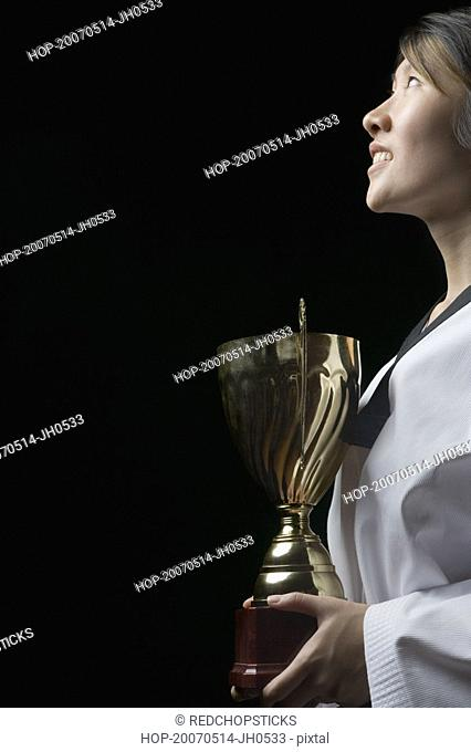 Side profile of a young woman holding a trophy