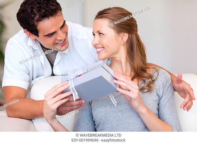 Young woman smiling happily about the present she just got from her boyfriend
