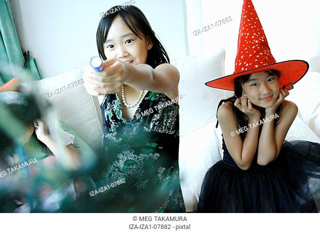 Girl pulling a party popper with her sister covering her ears with her hands