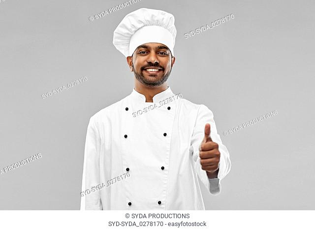 happy male indian chef in toque showing thumbs up