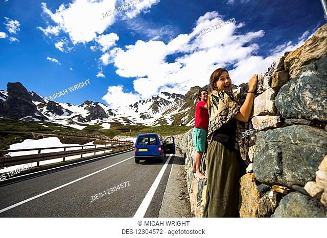A couple holding on to a rock wall along the Great St. Bernard Pass, one of the most ancient passes through the Western Alps