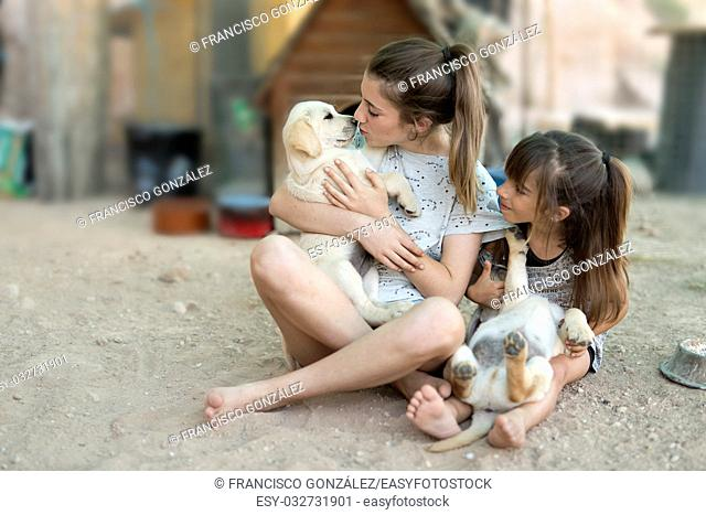 Portrait of two sisters with a golden retriever puppy