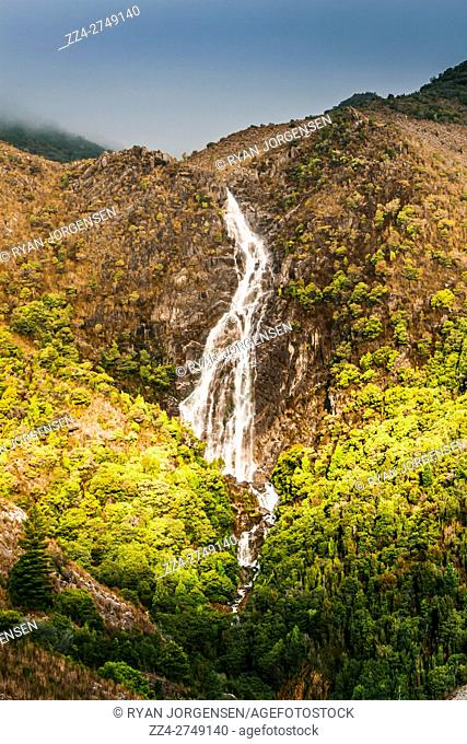 Scenic view of Horsetail falls in Queenstown mountains under cloudy sky in sunlight