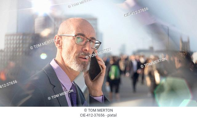 Serious businessman talking on cell phone on busy urban street