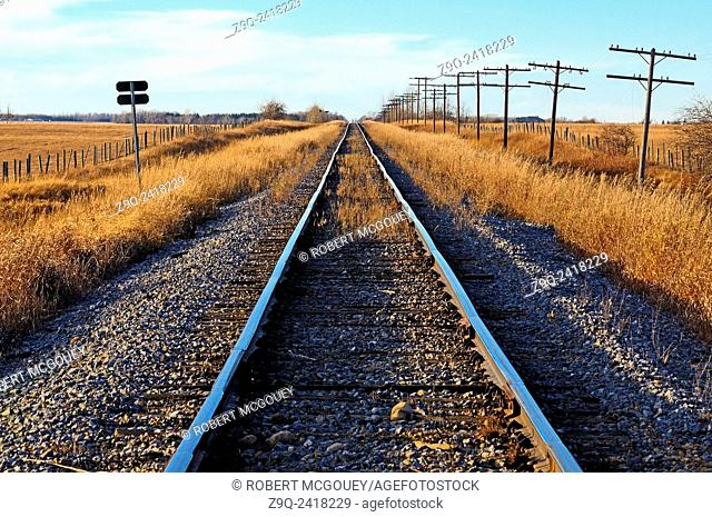 A landscape image of a set of railway tracks traveling straight to the horizon in rural Alberta, Canada