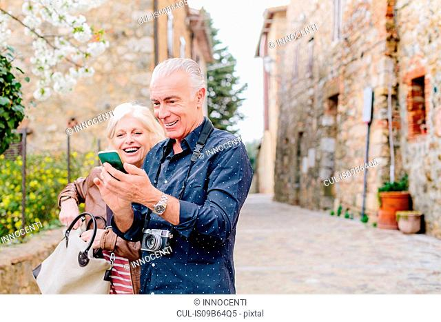 Tourist couple looking at smartphone on cobbled street, Siena, Tuscany, Italy